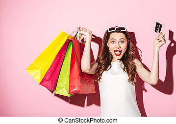 Happy young brunette woman holding credit card and shopping...