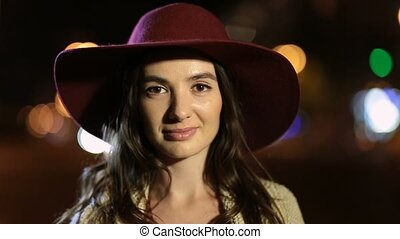 Beautiful woman with enigmatic smile at night - Portrait of...