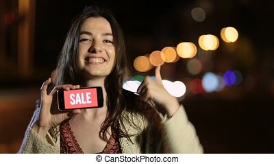 Woman showing smartphone with sale advertising - Emotional...