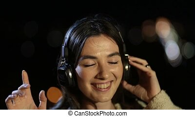 Girl listening to music with headphones at night - Portrait...