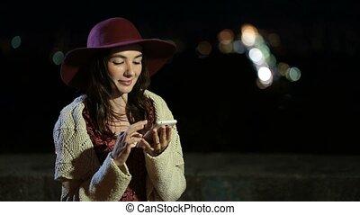 Stylish brunette woman using smartphone at night