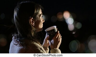 Smiling woman drinking coffee outdoors at night - Side view...