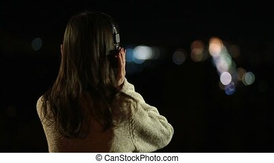 Woman in headphones listening to music at night - Back view...