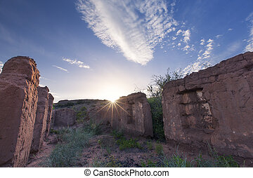 Ruins of old house with clouts at sunset with blue sky