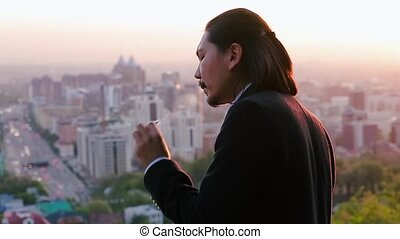 Stressed businessman smoking, coughing and looking at a...