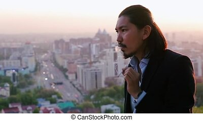 Stressed businessman smoking and looking at a marvelous city landscape in slow motion