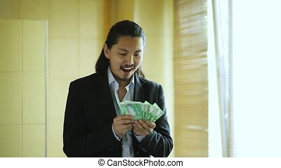Happy office worker dancing with money and celebrating pay raise
