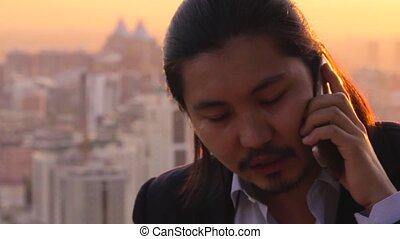 Rich businessman negotiating a deal over a phone against a...