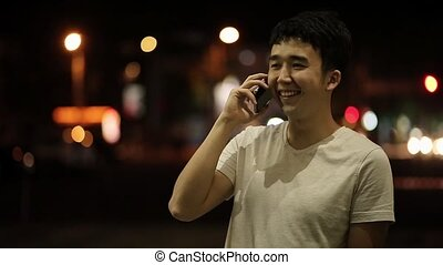Young man talking on a phone and laughing