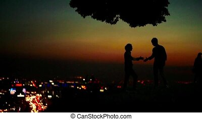 Two silhouetted businessmen standing on a hill and shaking hands in slow motion