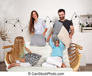 Young family and two children play at home fighting with pillows