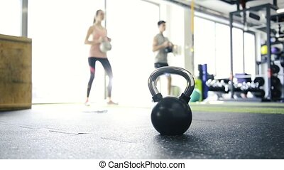 Young fit couple in gym exercising with kettlebell. -...