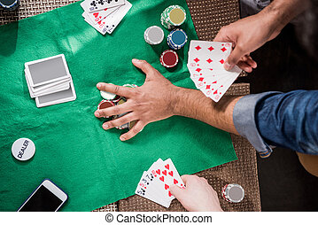 Men at gaming table - Close-up partial view of men with...