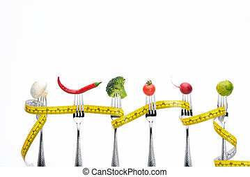 fresh vegetables on forks with measuring tape isolated on white, healthy living concept