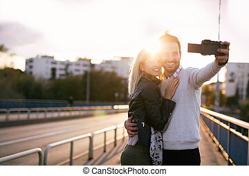 Beautiful young couple making selfie on bridge at sunset