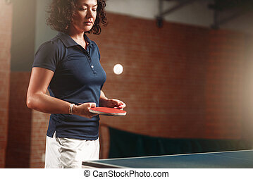 Table tennis, female player with racket hits ball