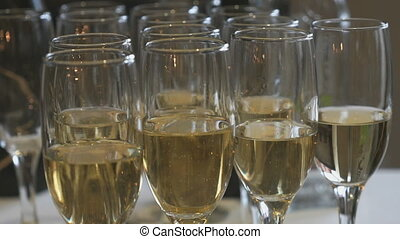 A lot of glasses with sparkling wine on table during the...