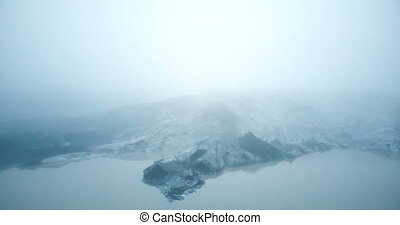 Aerial view of the glacier Merdalsjokull with volcanic ash in Iceland. Copter flying near the iceberg in lake, in fog.