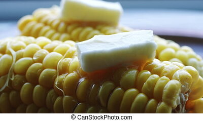 Hot cob of boiled corn with butter. - Piece of butter slowly...