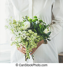 Young woman wearing white clothes holding flowers bouquet,...