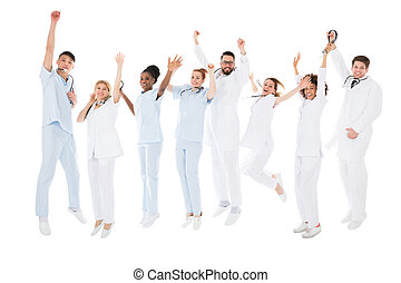 Group Of Happy Doctors Raising Their Arms Against White...