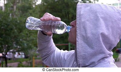 Young man drinking water after a fitness run