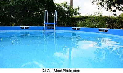 Swimming pool full of waving clear water in the garden.
