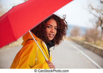 Woman looking camera in raincoat - Woman wearing yellow coat...