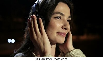 Romantic woman with earphones enjoying music - Closeup of...
