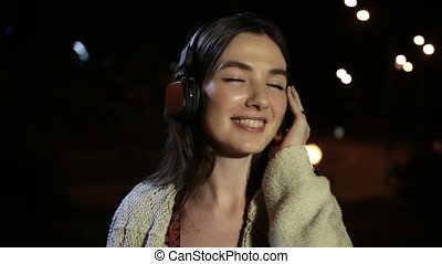 Beautiful woman enjoying music in night city - Cheerful...