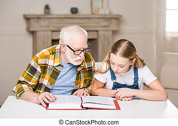 Grandfather and granddaughter sitting at table and reading book together