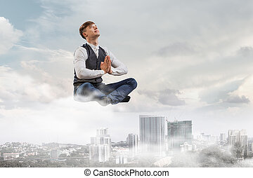 Take a deep breath and relax - Businessman in lotus pose...