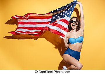 Happy young lady in swimwear holding USA flag. - Picture of...