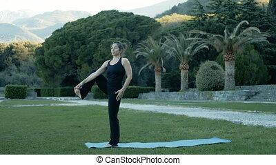 Adult woman performing stretching legs in park near trees....