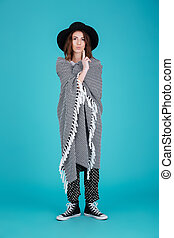Young funny woman in hat covered in blanket standing - Full...