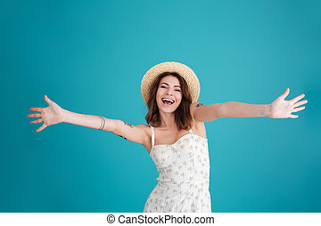 Young summer girl wearing hat and standing with outstretched...