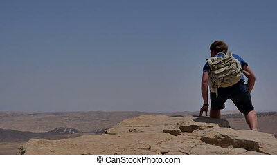 Young man with backpack sitting on cliff's edge and looking...
