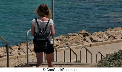 Young girl walking down the stairs to the sea. Professional...