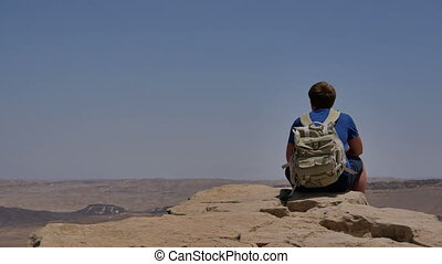 Young man with backpack sitting on cliff's edge and enjoying...