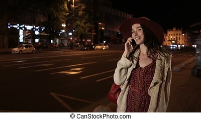 Beautiful girl using smortphone on street at night - Joyful...