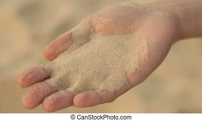 Sea sand is poured from women's hands - Pure sea sand in the...
