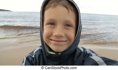 The boy takes pictures of himself against the sea