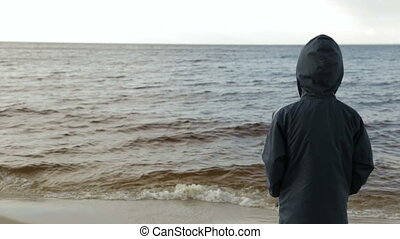 Boy looking at the sea, rear view - A boy looks at the waves...