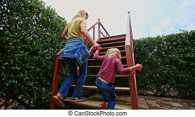 Mother Little Girl Climb up Stairs in Hedge Labyrinth in...