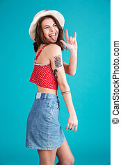 Funny naughty girl in hat showing rock sign with fingers -...