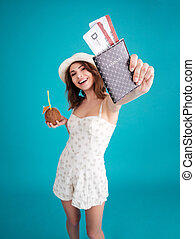 Girl traveller in summer clothes showing passport with...