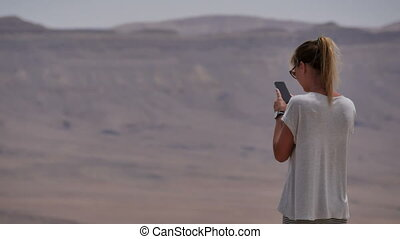 Young woman taking panoramic photo of the desert crater on her phone