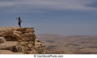 Young man standing on cliff edge and taking panoramic photo...