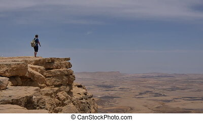 Man with backpack standing on the desert mountain rock cliff...