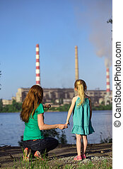 mother and daughter looking at the plant chimney-stacks